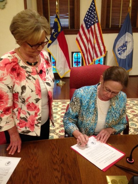 Chairman Beth Dawson signs the adoption of Plan NHC